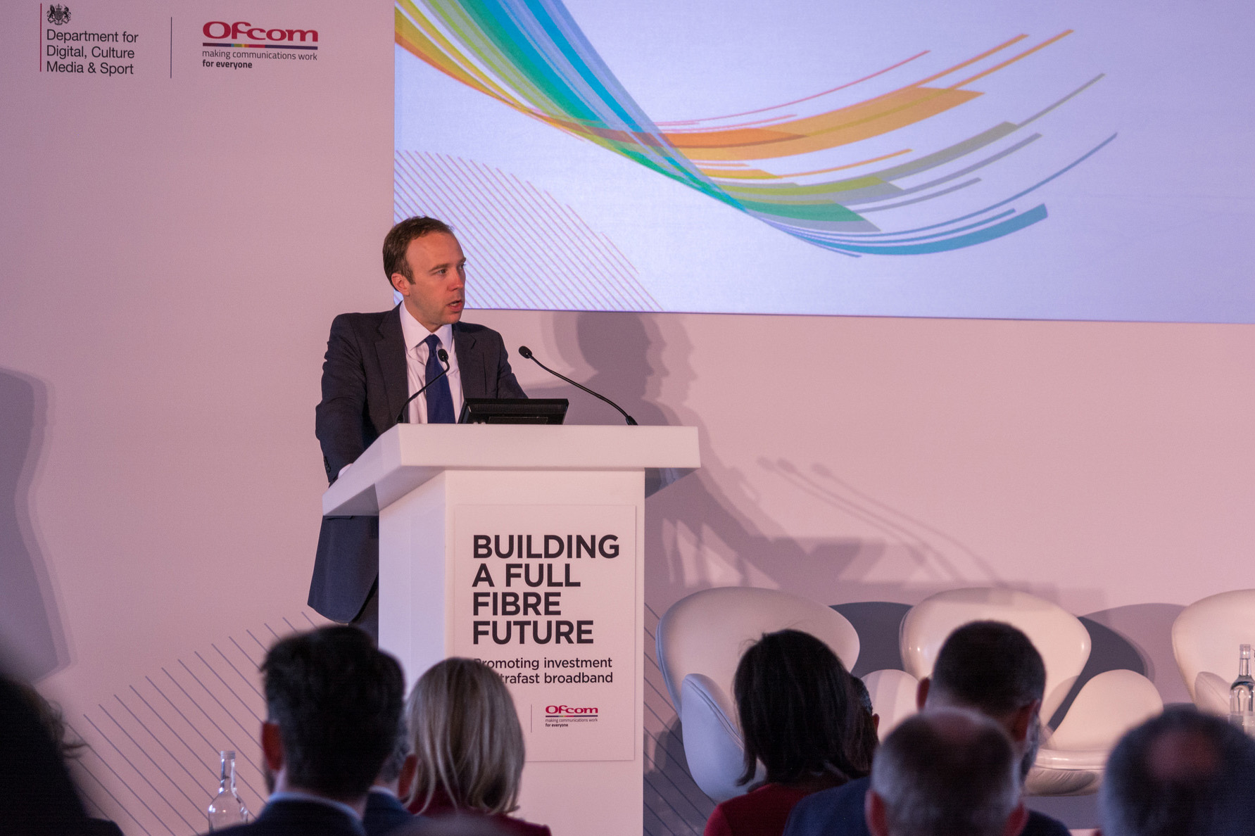 Man (Matt Hancock) speaking at podium on stage in front of an audience at the Building a Full-Fibre Future event