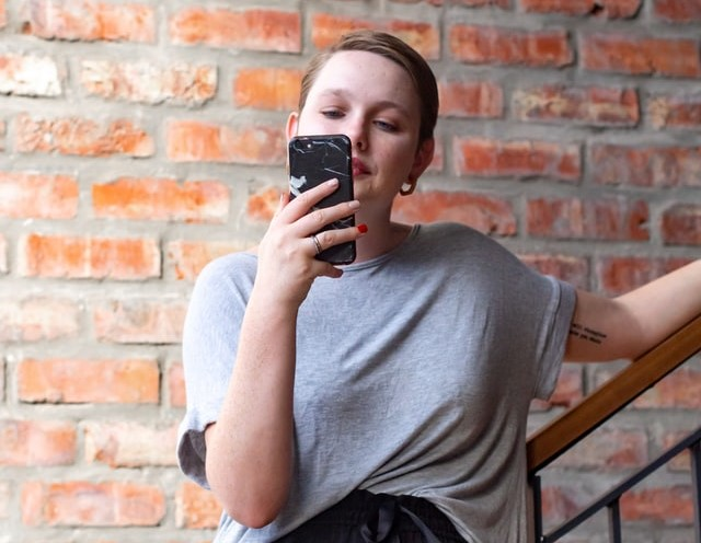 Woman on staircase against a red brick wall reading phone