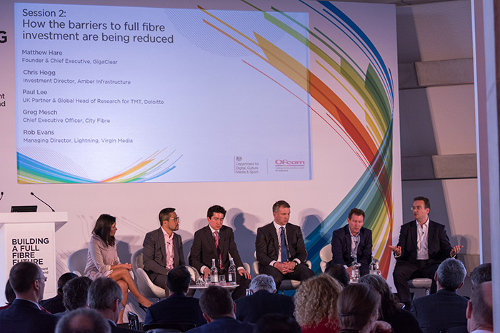 Panel of 6 people seated on stage in front of an audience, having an open discussion at the Building a Full-Fibre Future event