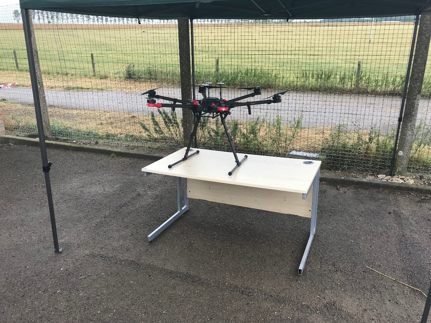 A drone stands atop a desk, outdoors but under cover. It is on display.
