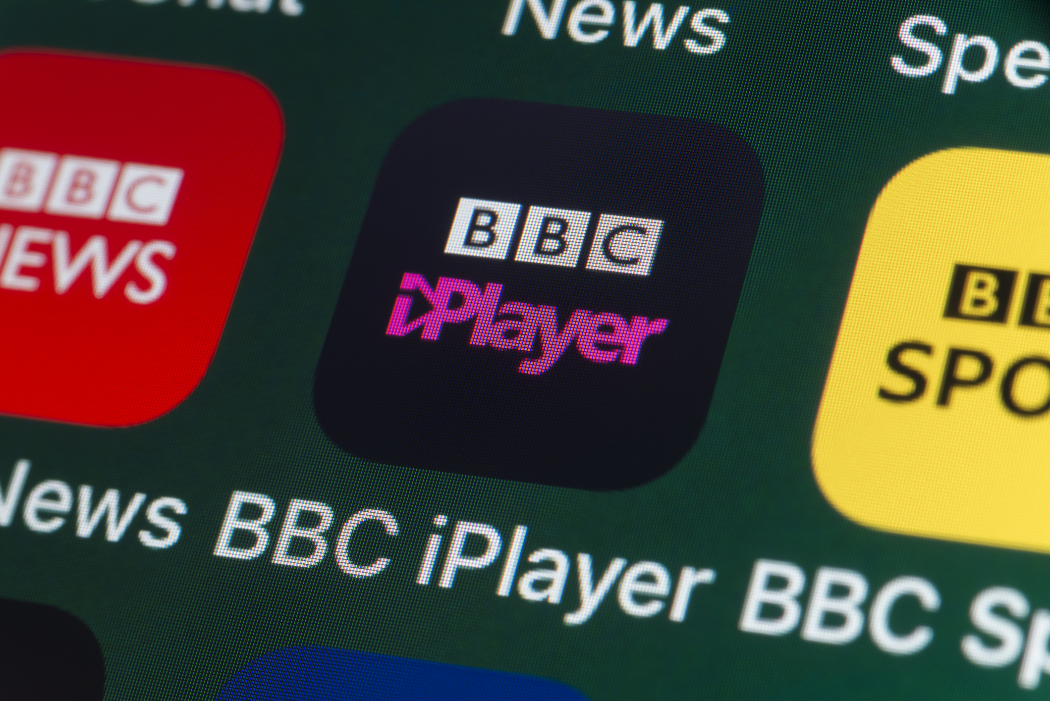 The buttons of the BBC iPlayer app, surrounded by BBC News, BBC Sport, News and other apps on the screen of an iPhone