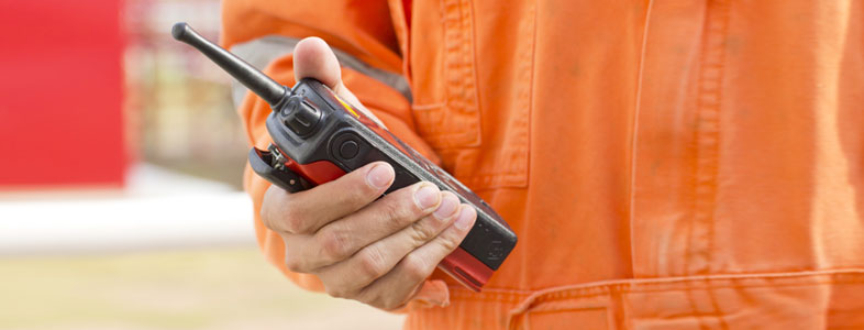 A man in overalls holding a walkie talkie